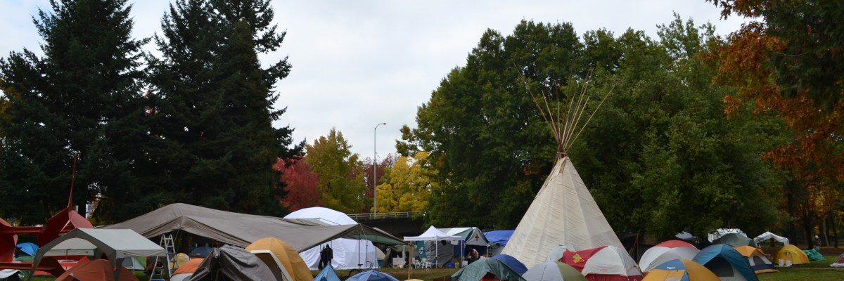 Photograph of a group of tents set up on a grass field in Washington Jefferson Park in Eugene. In the middle of all the tents stands a teepee. There is a line of dark green trees in the background beneath a gray sky.