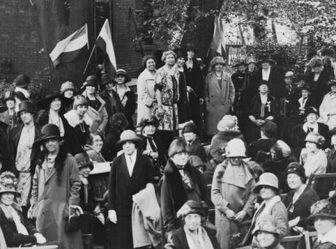 Black and white photograph of several dozen women gathering on a train platform to listen to a speech by Margaret Whittemore, an early woman's suffrage pioneer. Most of the women are well-dressed and are wearing an assortment of hats. There are virtually no men in the picture.