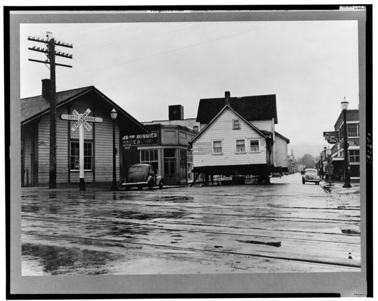Black and white photograph of a house being moved on wheels through downtown Cottage Grove, Oregon. The sky is gray and the streets are slick, suggesting that it had recently rained. There are traintracks in the foreground and a few old 1930s model cars.
