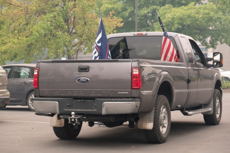 Photo of a charcoal gray pickup truck on a lifted suspension with no license plate and both an American flag and a Trump 2020 flag trailing behind. Photo taken at the site of the Holiday Farm Fire evacuation zone