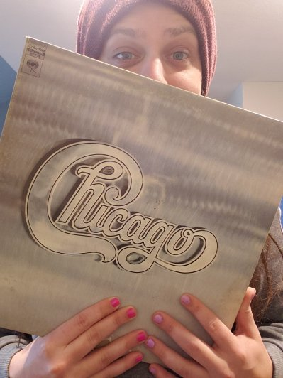 Photo of James holding a copy of Chicago II on vinyl, the second record by the band chicago. His head is poking over the top of the record, and his fingers are below the record, with nails painting pink and violet.