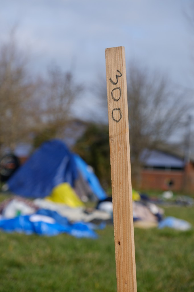 A wooden stake with the number 300 written with black ink stands in the foreground, while in the blurred background there is a tent with tarps and trash bags surrounding it.