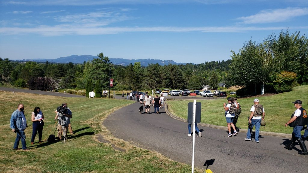 Photo of the idyllic scene outside New Hope Bible College, where a line of right-wingers are making their way down the driveway with rifles at their side and backpacks on. It's a sunny and blue-sky day, and the cascades can be seen in the distance.