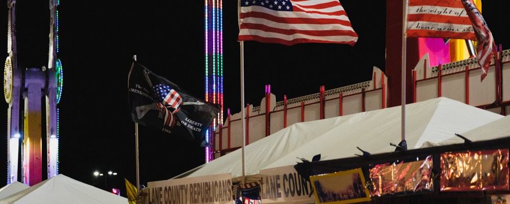 """Various American flags wave above a tent labeled """"Lane County Republicans"""" during a night at the fair."""