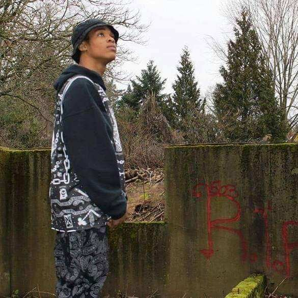 Jermelle Joseph Madison Junior is pictured standing in a yard, with a fence and some trees in the background. Madison is wearing a hoodie, patterned vest, and a bucket hat while looking off into the distance.