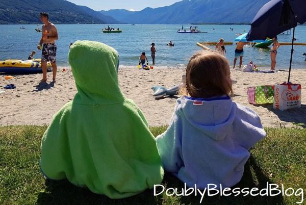 Zwillinge in Badeponchos sitzen am Strand und sehen auf das Wasser