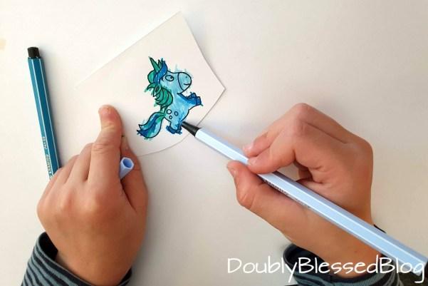 Kind malt Einhorn mit Stabilo Pen68 Filzstift aus