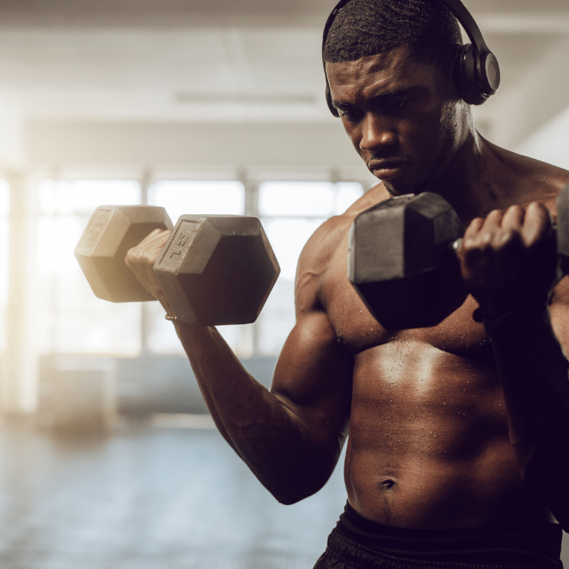 man with headphones curling dumbbells for workout plans area