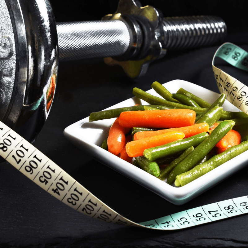 Veggies, measuring tape, and dumbbell image for health and fitness articles