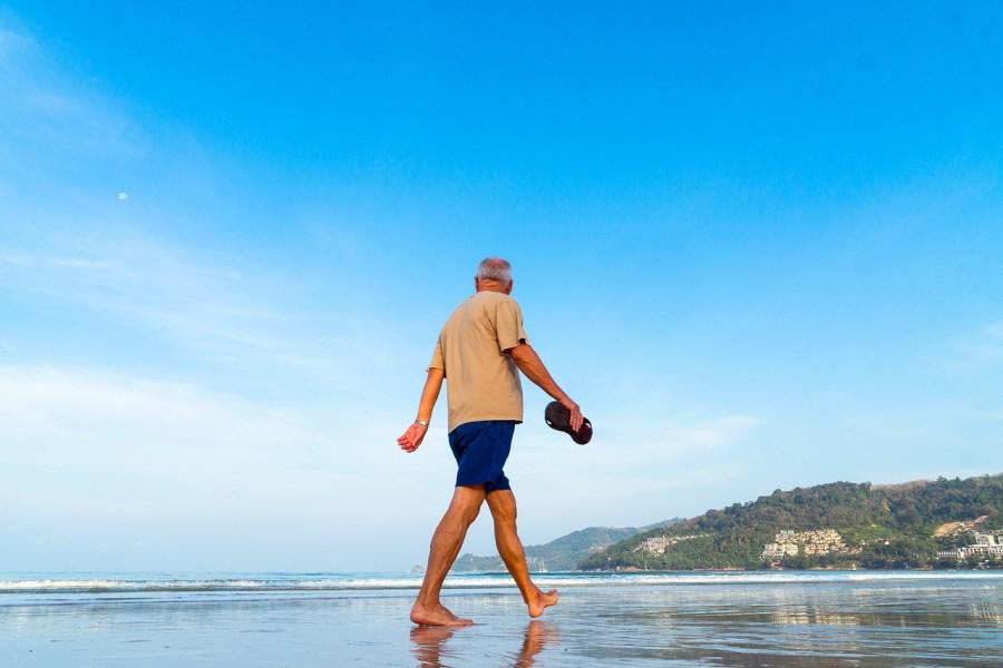 senior walking in the sand