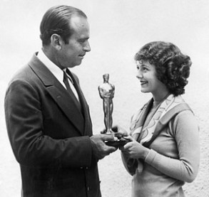Douglas Fairbanks Sr. presents an Oscar to Janet Gaynor. (Photo Credit: The Guardian)