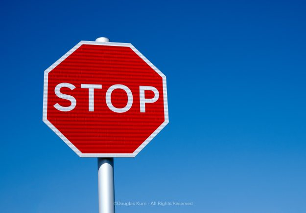 """A red octagonal STOP sign against a blue sky used to illustrate a post on """"stoppers"""". Photo by Douglas Kurn"""