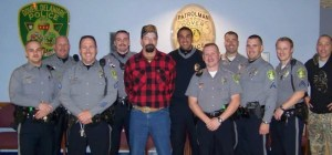 SSG. Dave Green takes a photo with Dover Police officers prior to hitting the streets on a ride along.