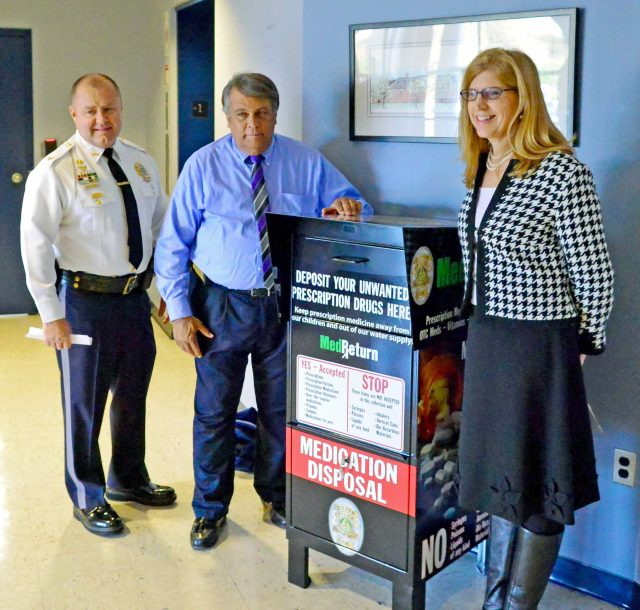 Dover Police Chief Paul Bernat, Dover Mayor Robin Christiansen, and Director of Delaware Department of Public Health, Dr. Karryl Rattay stand with the Dover Police Department's new medication drop box after the unveiling.  The box is now available for public use 24 hours a day, 365 days a year.