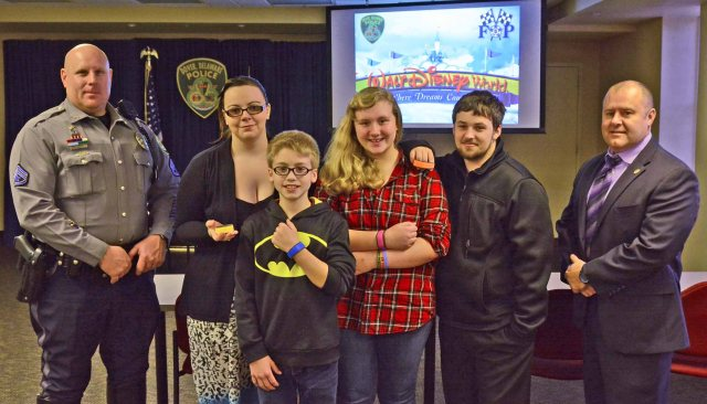 The family was presented with their magic wristbands for their trip to Disney World. Left to Right: MCpl. Dave Gist (President of the Dover FOP), Alexis, Christopher, Emily, John, and Dover Police Chief Paul Bernat