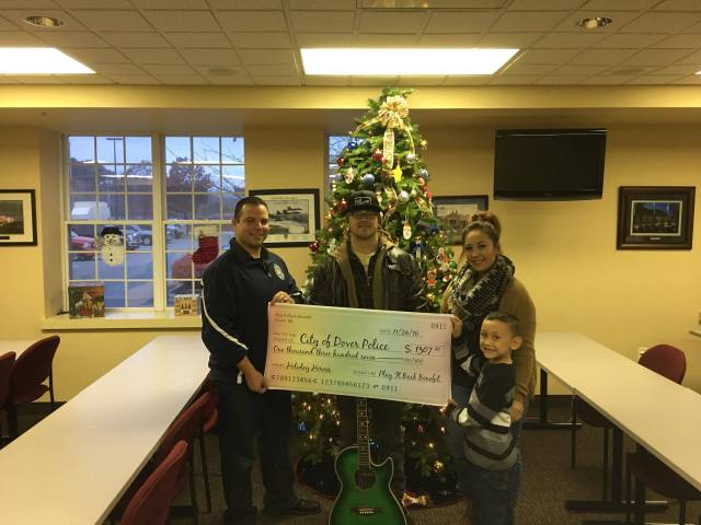 """M/Cpl. Mark Hoffman receives the """"Play It Back"""" check from Dave Nickolson, Kathy Nicolson, and their son Kade"""