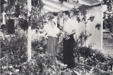 black and white photo of two people standing in a garden room