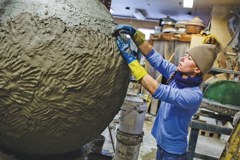 woman working on large clay urn