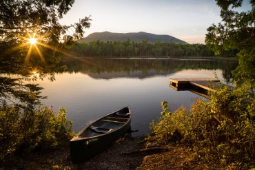 canoe on land next to lake and mountians