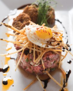 Steak tartare with a quail egg and bone marrow croutons.