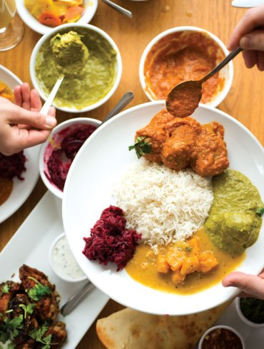 A shareable meal of lamb meatball curry, palak paneer, and butternut-squash and beetroot curries.
