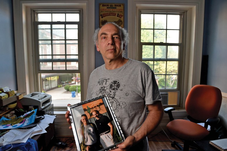 Ken Eisen holds a picture of himself with the late director Jonathan Demme.