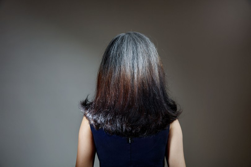 Back of a woman's head with gray hair and dyed ends.