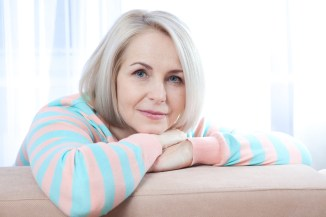 Middle-aged woman leaning over couch