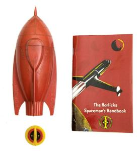 This Spaceship Cup and Cap Badge were originally offered in a promotion where you sent in sixpence or a shilling with a label from your Horlicks jar to get them. Between 1951-56 the beverage maker sponsored the Dan Dare Radio Show on Radio Luxembourg and young listeners were encouraged to enrol in the Horlicks Spacemans Club when they tuned in at 7.15, a mug of steaming Horlicks on the kitchen table, to hear Bob Danvers-Walker announce, 'Dan Dare - Pilot Of The Future, brought to you by Horlicks – The food-drink of the night...' Image: ComPal