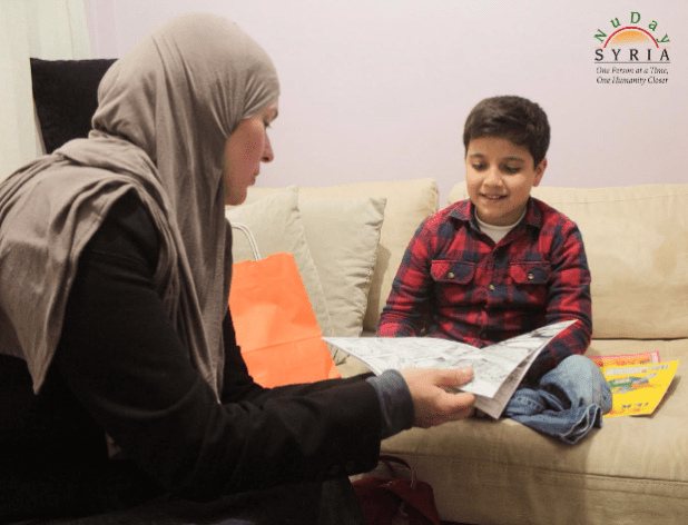 A Syrian refugee receives copy of Haawiyat