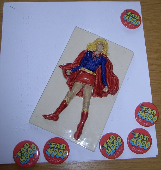 A ceramic Supergirl across a page of braille. This was created by the children of St Vincent's School for the Blind in Liverpool as a gift for Supergirl actress Chyler Leigh on her visit to the school this week. Photo courtesy Tim Quinn