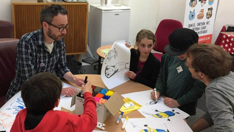 Ace artist Marc Jackson is taught how to draw properly by Lancaster's budding comic creators! Photo: John Freeman