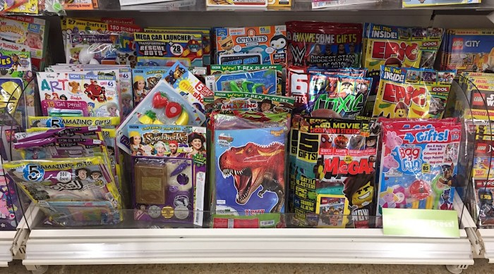 Some of the many titles aimed at younger readers. on sale in Sainsbury's, Lancaster in February 2019. Most come bagged with a toy as an incentive, but parents seem increasingly uncomfortable at the amount of plastic included