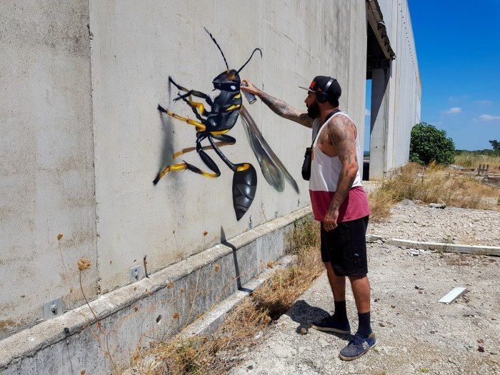 Artist Odeith puts the finishing touches to an image of a mud wasp. Image: Odeith Official Site