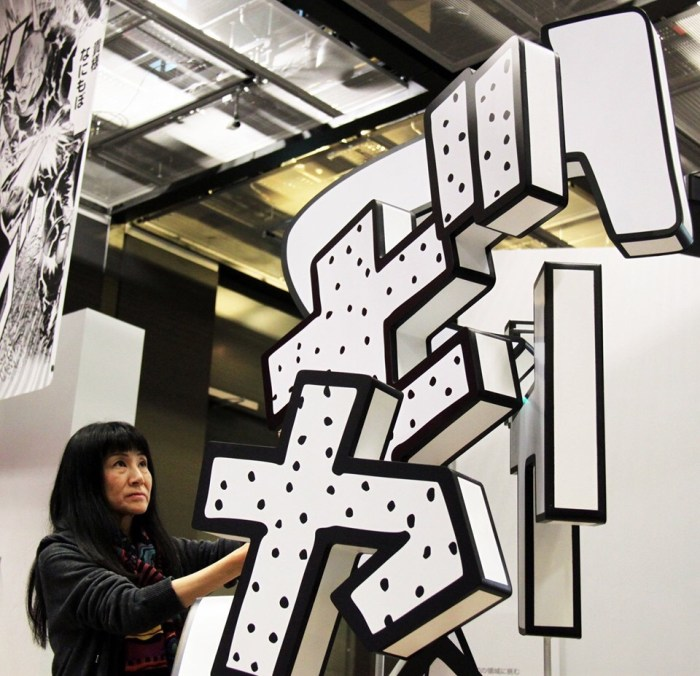 """Artist Rieko Akatsuka installs her dynamic sculpture inside the MANGA exhibition at the British Museum, which opens this week. Akatsuka's father was a pioneering manga artist and she was inspired by his use of onomatopoeia for the sound of laughter. This piece uses randomly placed letters taken from the manga so """"a viewer can compose their own laughter depending on where they're positioned."""" Photo: British Museum"""