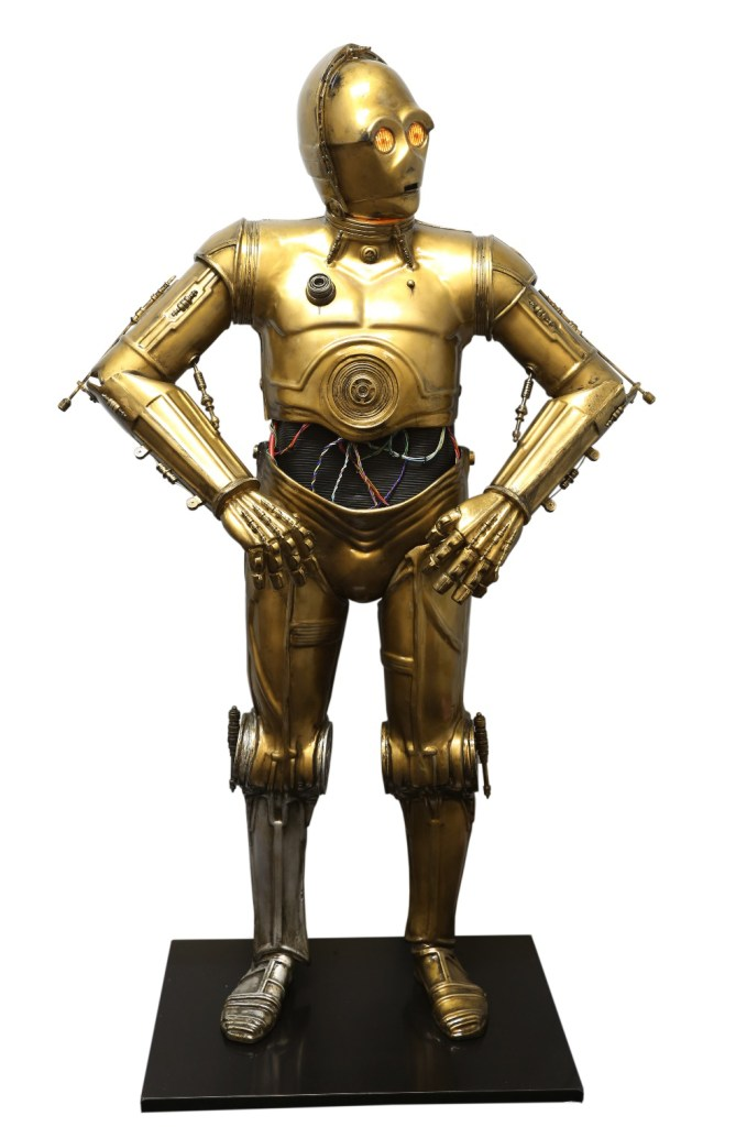 Star Wars - Life size kit built C3PO as seen in the George Lucas epic. On base, with vacuum formed plastic sections that slot together. It has been wired so the head lights up. It breaks down into sections for easier transportation. 170 cm high. The kit was shown to Gordon Tarpley a leading C3PO builder and in the USA who believes it's from a company called Golden Armour.