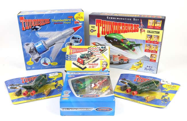 Thunderbirds Toys including Matchbox BBC Radio Times Commemorative Set, Carlton Thunderbird 1 electronic playset, Diecast 5 Vehicle set, ticking alarm clock by Wesco, two Carlton Thunderbird 2 models, all boxed. Image: Ewbanks