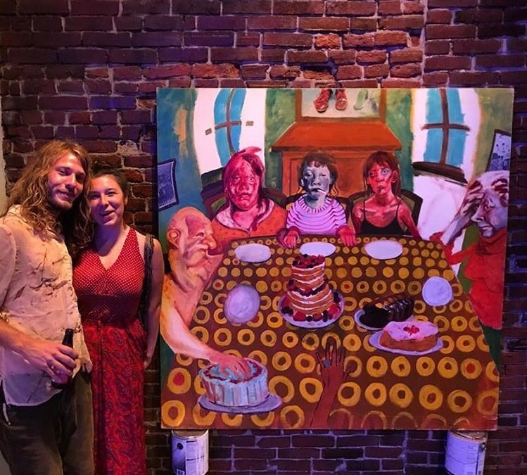 Artist Sarena Johnson and her boyfriend next to a piece of hers that sold at the event.
