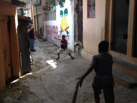 Boys playing baseball with a piece of wood for a bat in a Herrera passageway