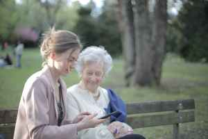 daughter explaining elderly mother how using smartphone