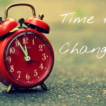 """A photo of a red alarm clock with the words, """"Time for Change"""" written on the right hand side."""