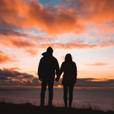a couple walking into a sunset