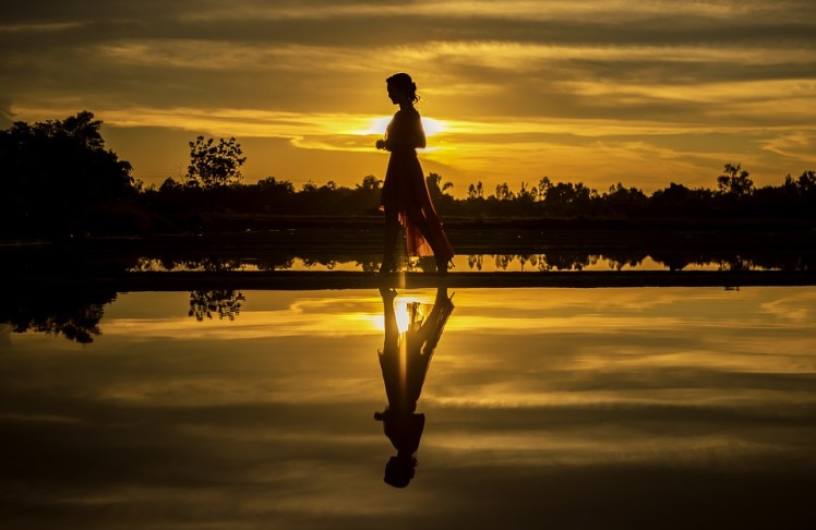 A picture of a girl at sunset with her reflection in a lake.