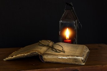 Ancient book near a candle