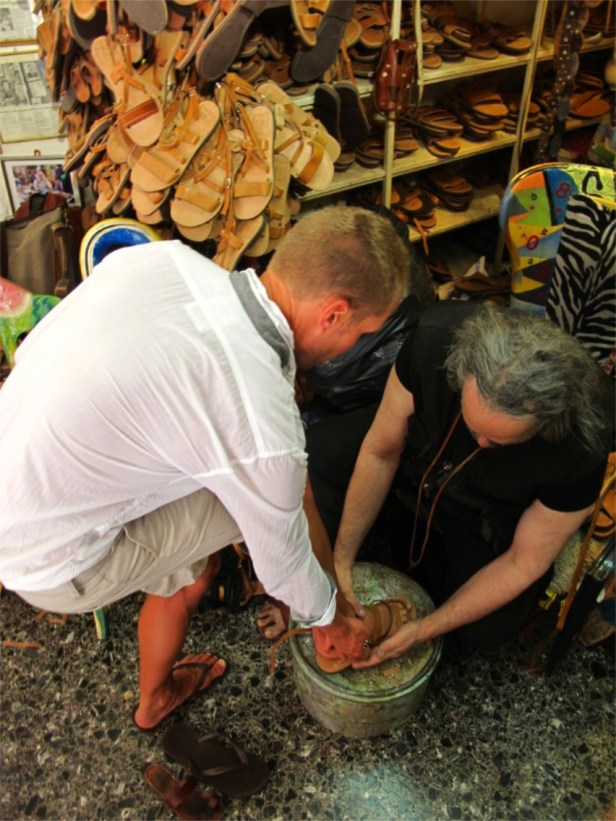 Pantelis kneels and fits each sandal till he is content and suggests we condition it with olive oil to keep it supple.