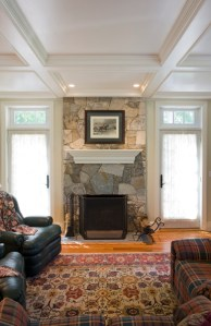 stone fireplace and wood coffered ceiling