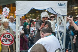 The 'Atos Miracle Cure' -'Atos's own Reverend' blesses and lays his hand on the head of a man in a wheelchair at the Closing Atos Ceremony by DPAC & UK Uncut outside Atos's offices.
