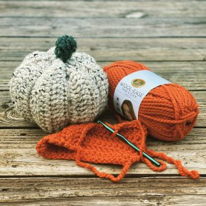 crocheted pumpkins on wood background with yarn and crochet hook