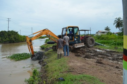Excavator clearing drainage canal in Region Five