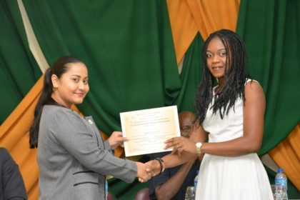 Ms. Adeti DeJesus, of the Office of the Presidential Advisor on Youth Empowerment presents a certificate to one of the participants at the graduation ceremony